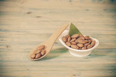 Almonds in bowl on wood Stock Images