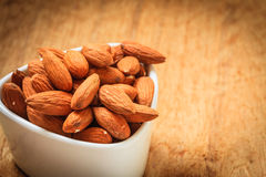 Almonds in bowl on wooden background Royalty Free Stock Photos