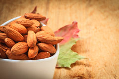 Almonds in bowl on wooden background Royalty Free Stock Photography