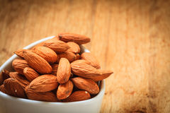 Almonds in bowl on wooden background Stock Photos