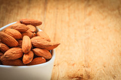 Almonds in bowl on wooden background Royalty Free Stock Images