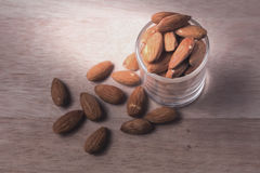 Almonds in brown bowl on wooden Stock Photo
