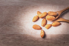 Almonds in brown bowl on wooden Stock Photography