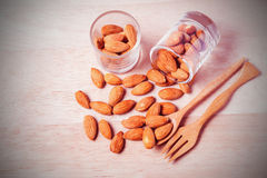 Almonds in brown bowl on wooden Stock Images