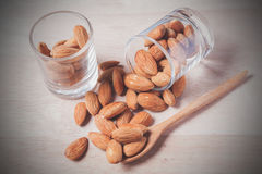 Almonds in brown bowl on wooden Royalty Free Stock Image