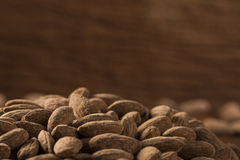 Almonds in brown bowl on wooden background Stock Images