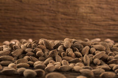 Almonds in brown bowl on wooden background Stock Image