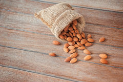 Almonds in brown bowl on wooden background Stock Photography