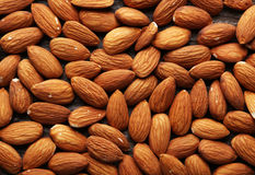 Almonds on brown wooden background. Royalty Free Stock Photos