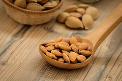 Almonds on brown wooden background Stock Photos