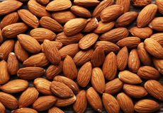 Almonds on brown wooden background Royalty Free Stock Photo