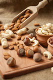 Almonds, cashew  peanut,  hazelnuts in wooden bowls on wooden and burlap, sack background Stock Image