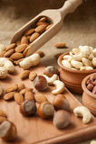Almonds, cashew  peanut,  hazelnuts in wooden bowls on wooden and burlap, sack background Royalty Free Stock Photography