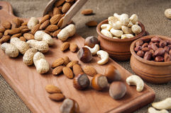 Almonds, cashew  peanut,  hazelnuts in wooden bowls on wooden and burlap, sack background Royalty Free Stock Photos
