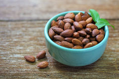 Almonds a ceramic bowl on grained wood Stock Images