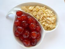Almonds and Cherries. A simple, white dish of sliced almonds and glace cherries Royalty Free Stock Photography
