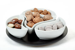 Almonds in chocolate and walnuts on white Royalty Free Stock Photos