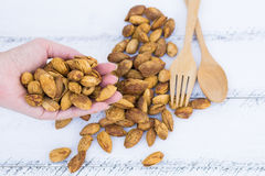 Almonds. Close up woman`s hand hold almonds under table with spoon Stock Photo