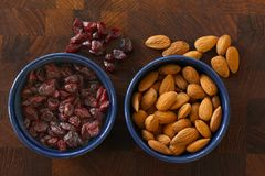 Almonds and cranberries lying in  blue bowls on dark wooden background with almonds and cranberries scattered around. Top view ima. Almonds and cranberries lying royalty free stock photos