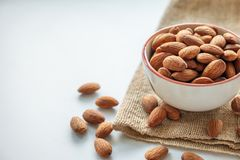 Almonds in cup on sack stock image