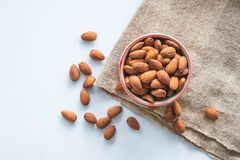 Almonds in cup on sack royalty free stock image