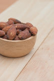 Almonds in cup on wooden background Stock Photo