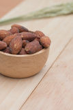 Almonds in cup on wooden background Stock Image