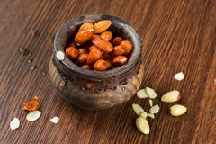 Almonds in wooden bowl on wooden table. Almonds in decorative wooden bowl on wooden table Stock Photography