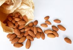 Almonds duper nutritious and healthy food. Almonds pour out of a paper bag on white background. Super nutritious and healthy food Stock Image