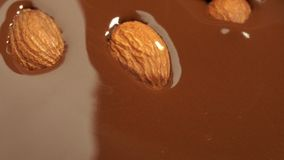 Almonds fall into melted chocolate. 4K UHD 3840x2160 Video Clip royalty free stock photo