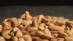 Almonds falling down on table. 4K stock footage