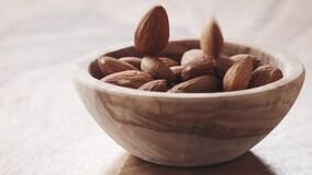 Almonds falling in wood bowl on wooden table in slow motion