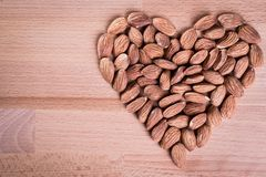 Almonds forming a heart-shape on wooden floor background. Nuts food healthy natural diet snack seed nature group organic tasty ingredient vegetarian raw heap royalty free stock photos