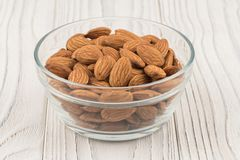 Almonds in a glass bowl on white old wooden table. Royalty Free Stock Photos