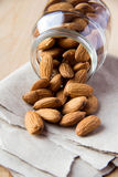 Almonds in a glass jar. On wooden table and paper Royalty Free Stock Photo