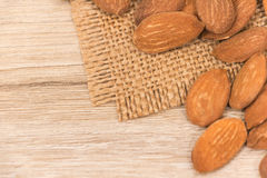 Almonds. Golden almonds on wooden background stock photo