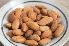 Almonds in a green ceramic dish on the wooden table. stock photos