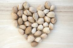 Almonds in hard shells, group of nuts on wooden table. Sunlight, one by one in heart shape, romantic love royalty free stock photos