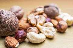 Almonds, Hazelnuts, Cashew Nuts and Whole Walnuts on Golden Background. Healthy Organic Snack, Breakfast, Food Ingredients.  stock images