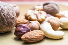 Almonds, Hazelnuts, Cashew Nuts and Whole Walnuts on Golden Background. Healthy Organic Snack, Breakfast, Food Ingredients.  royalty free stock photo