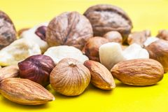 Almonds, Hazelnuts, Cashew Nuts and Whole Walnuts on Yellow Background. Healthy Organic Snack, Breakfast, Food Ingredients.  stock photos