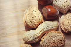 Almonds, hazelnuts and peanuts on a wooden board Royalty Free Stock Images
