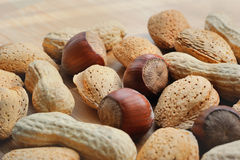 Almonds, hazelnuts and peanuts on a wooden board Stock Photography