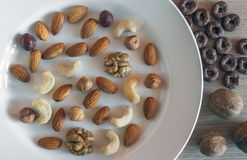 Almonds, Hazelnuts, Walnuts, Cashew Nuts on a White Plate, Three Whole Walnuts, Crunchy Whole Grain cereals round oats on Light. Wooden Table. Healthy Organic stock photos