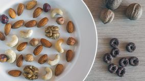 Almonds, Hazelnuts, Walnuts, Cashew Nuts on a White Plate, Three Whole Walnuts, Crunchy Whole Grain cereals round oats on Light. Wooden Table. Healthy Organic stock photo