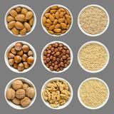Almonds, hazelnuts and walnuts in white bowls royalty free stock photo