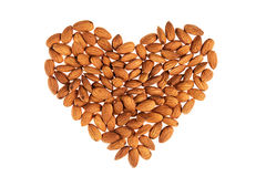 Almonds heap in heart shape on white background. Stock Photography