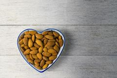 Almonds in heart shape dish. On white wooden Stock Photos