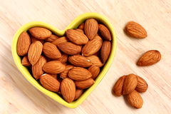 Almonds. In a heart-shaped plate close-up Royalty Free Stock Images