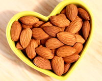 Almonds. In a heart-shaped plate close-up Royalty Free Stock Photography